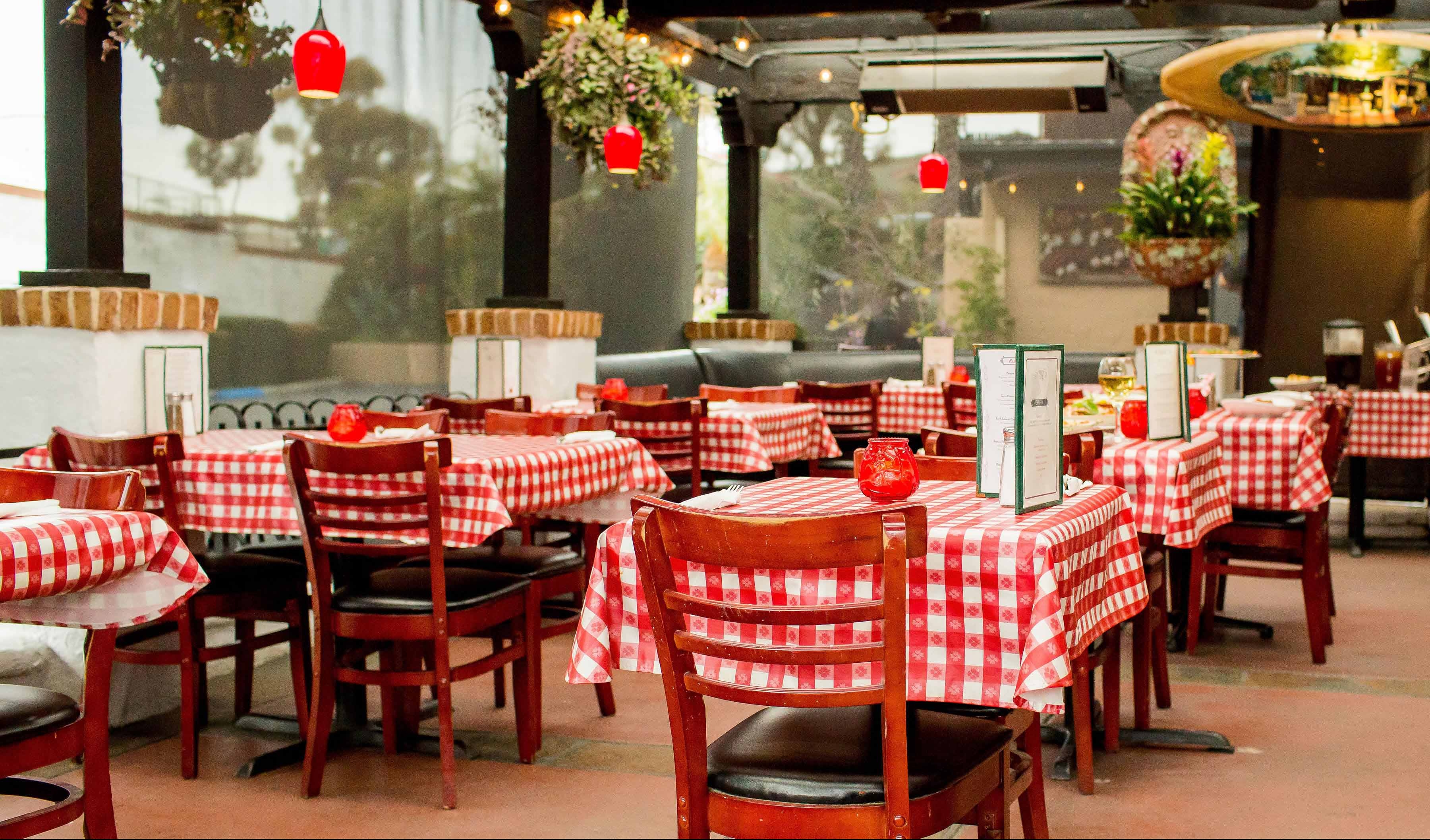 Sonny's Outdoor Covered patio seating with red and white table clothes and hanging lights